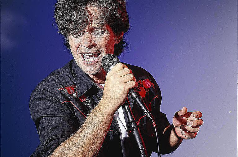 Portrait of American musician and singer John Cougar Mellencamp while holding a microphone and singing.