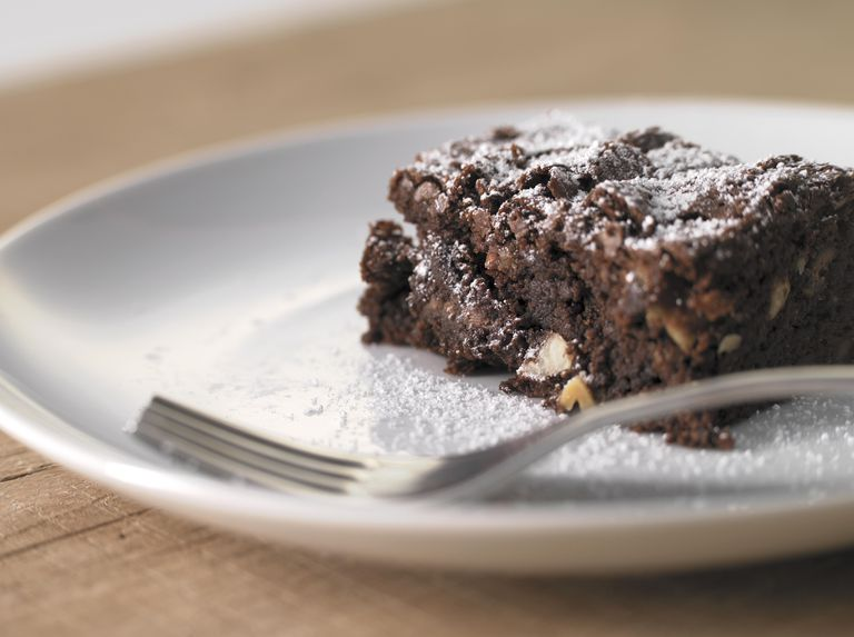 Chocolate brownie with nuts on plate, close-up