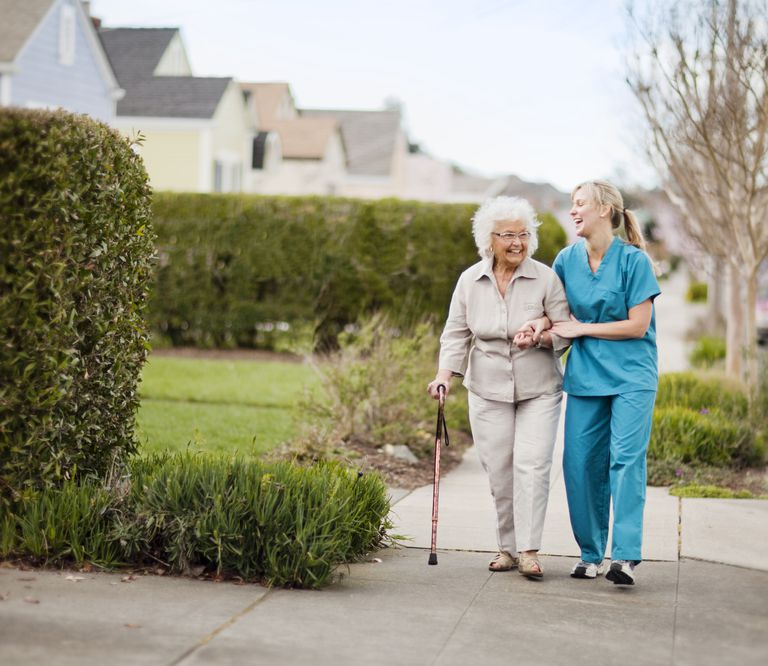 Home health aide helping elderly woman on a walk