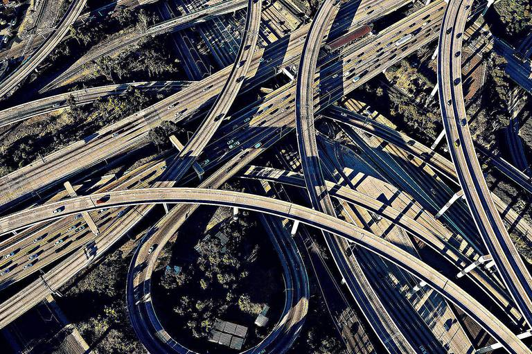 A flyover view of a complex freeway intersection in Los Angeles illustrates the modern city and lifestyle that results from the view of modernization theory.