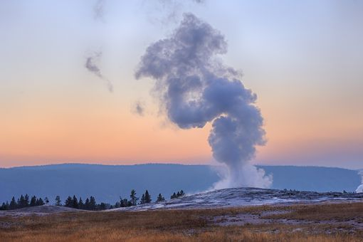 Old faithful geyser erupting with sunset in the background