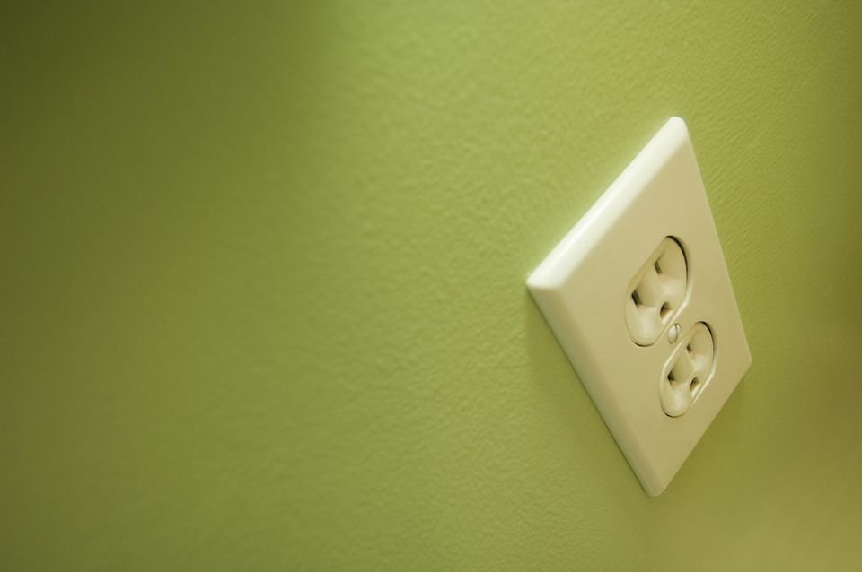 White electrical outlet on a green wall