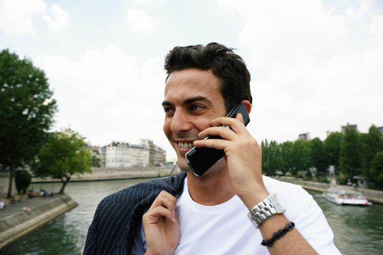 France, Paris, man standing on bridge using mobile phone, smiling