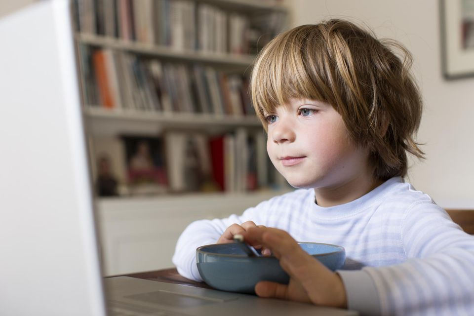 Young boy eats breakfast watching a laptop