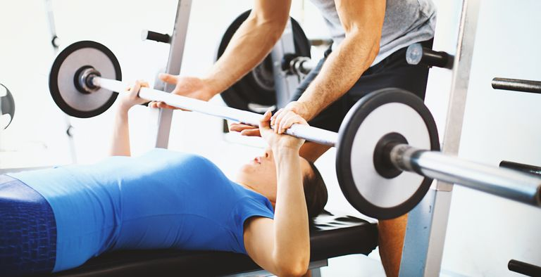 woman doing a bench press with a spotter
