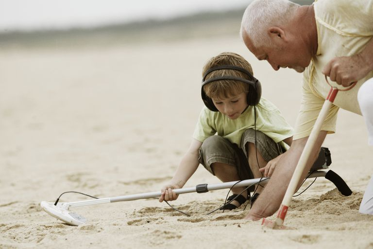 A child and his grandfather using a metal detector.