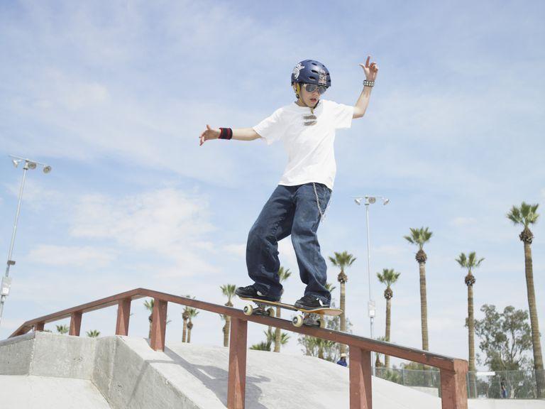 Boy (10-12) riding skateboard down rail