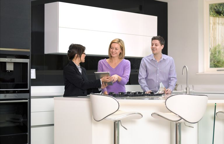Estate agent with couple in new build house