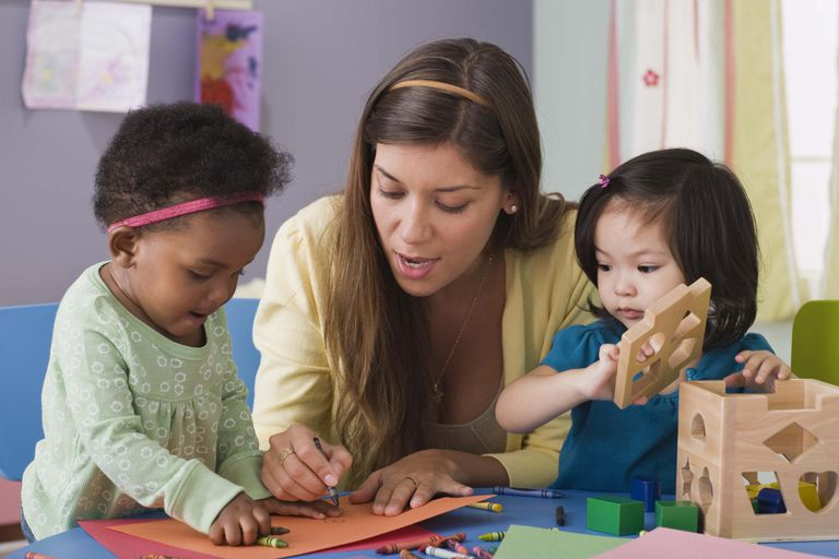Teacher helping toddlers color at daycare