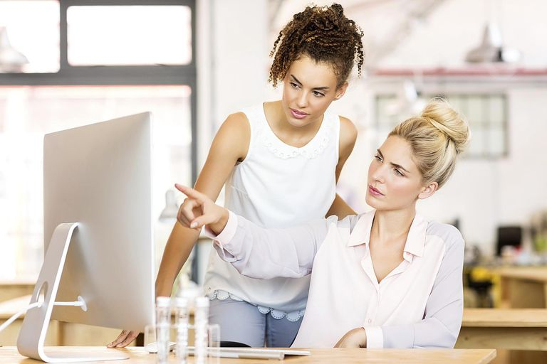 Businesswoman Explaining Strategy To Female Colleague On Computer