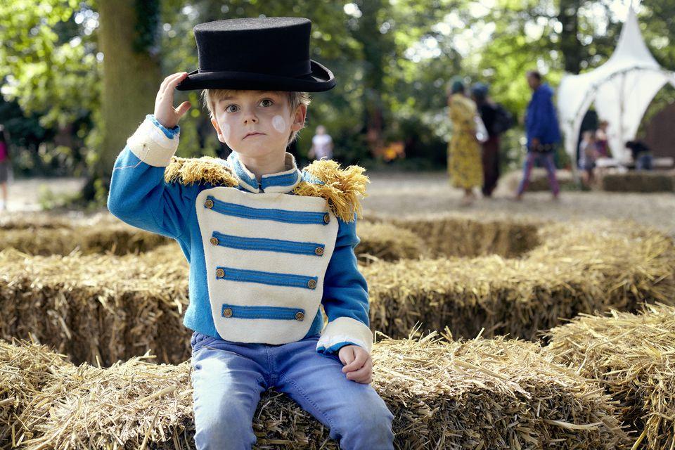 boy in fancy dress sitting on a hay bale