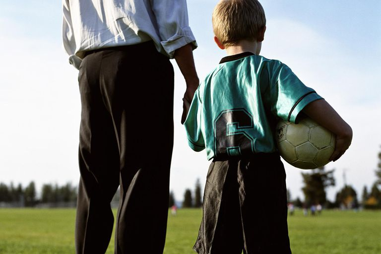 Father and son at soccer field with ball