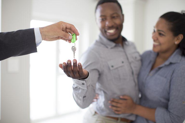 Realtor giving couple keys to new home
