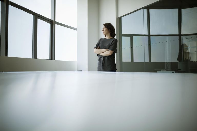Businesswoman with arms crossed looking out