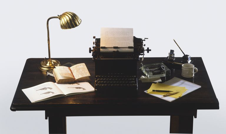 Golden desk lamp, open books, old-fashioned typewriter and writer's equipment on wooden desk, high angle view.