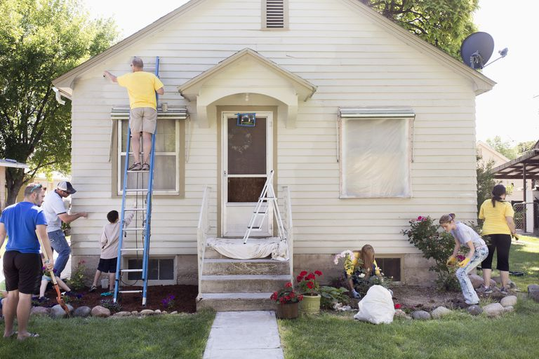 Neighbors helping paint a house.