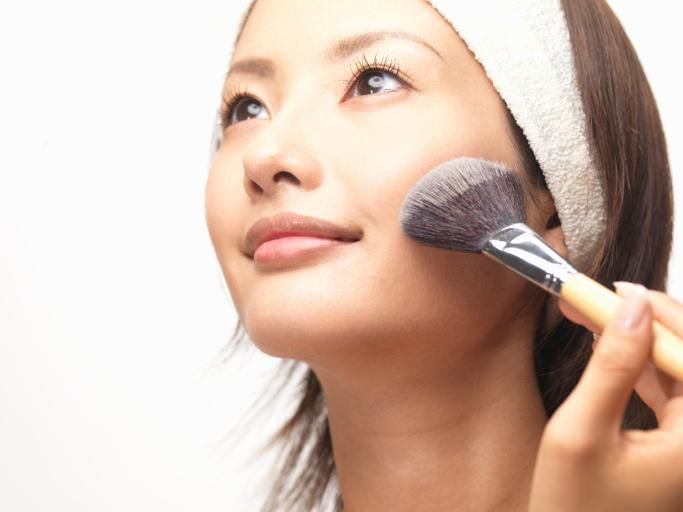 Asian woman using foundation