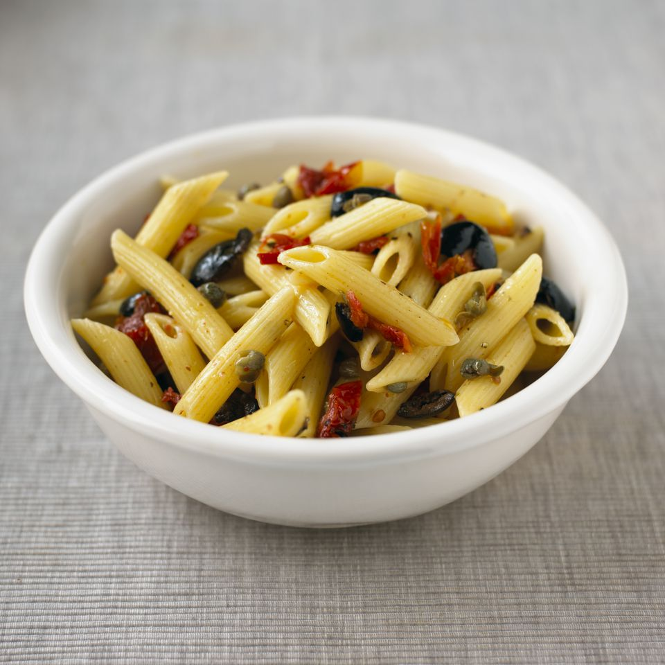 Storecupboard pasta made from penne with capers, olives and sundried tomatoes, served in white bowl on table