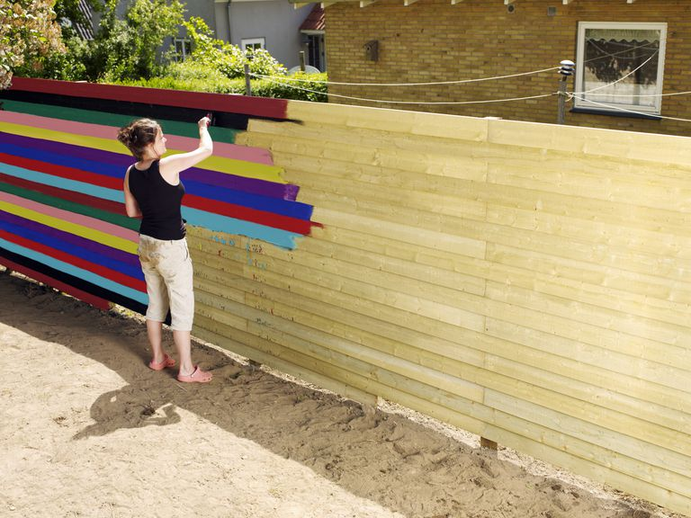 Woman painting fence in different colour