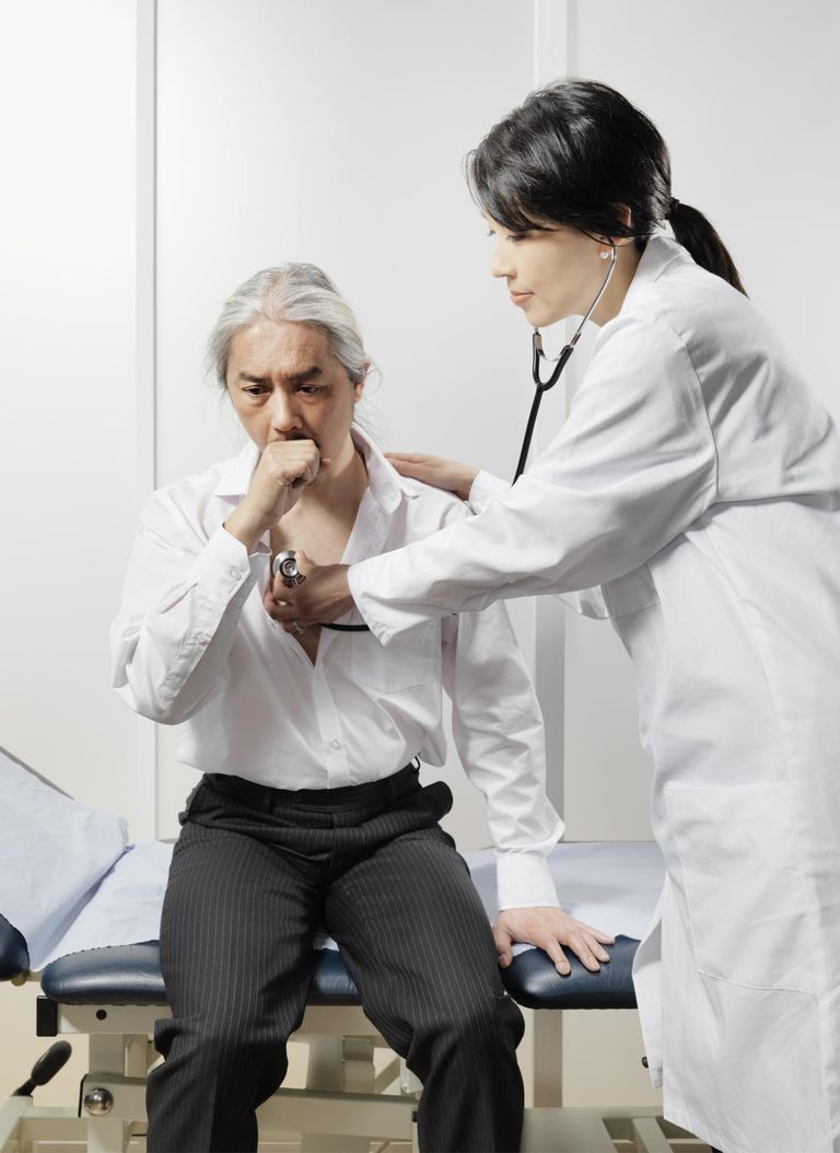 man coughing with female doctor listening with stethoscope