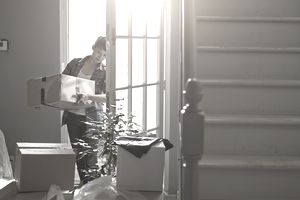 woman carrying box out door