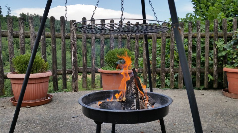 Burning Fire Pit In Back Yard Against Railing