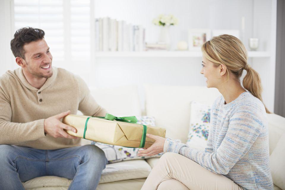 Man giving girlfriend gift on sofa