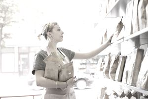 Shop employee stacking shelves in delicatesse shop