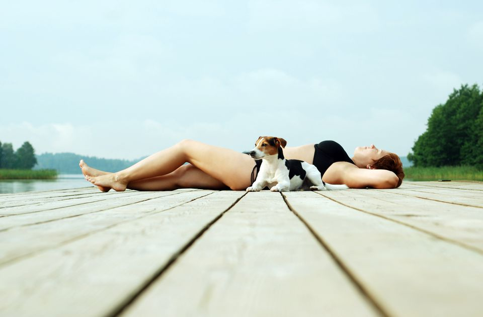 Full Length Of Woman With Dog Lying Down On Pier Against Sky