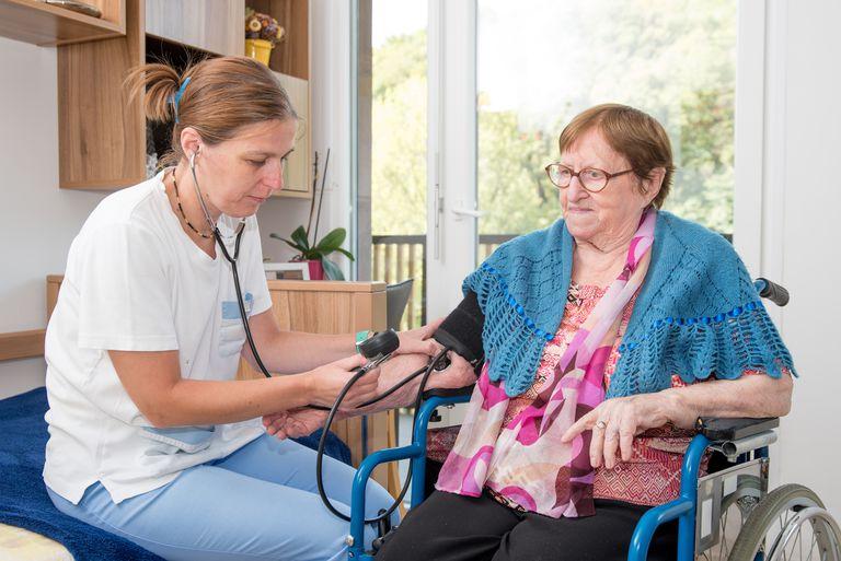 Nurse Checking Blood Pressure of Senior Female Patient