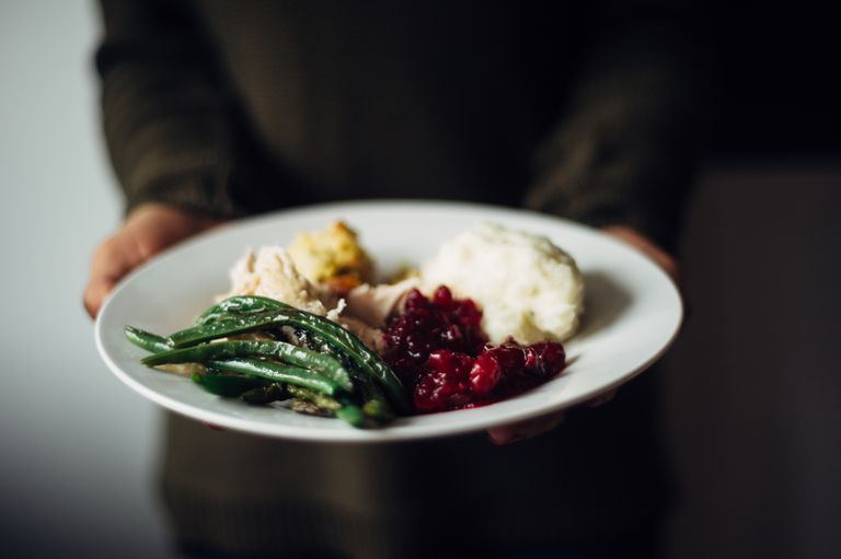 Plate with greenbeans, mashed potatoes, turkey, and cranberries