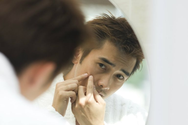 Man examining pimple in mirror