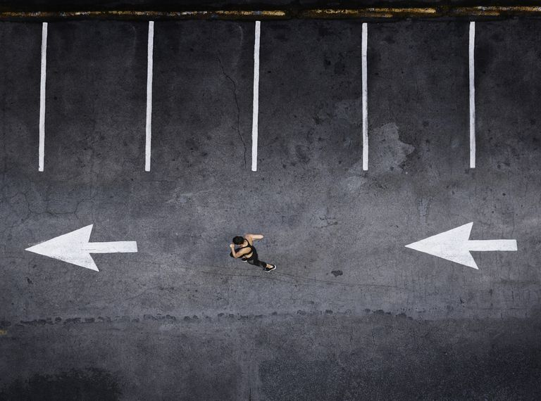 Aerial view of Pacific Islander woman running in parking lot