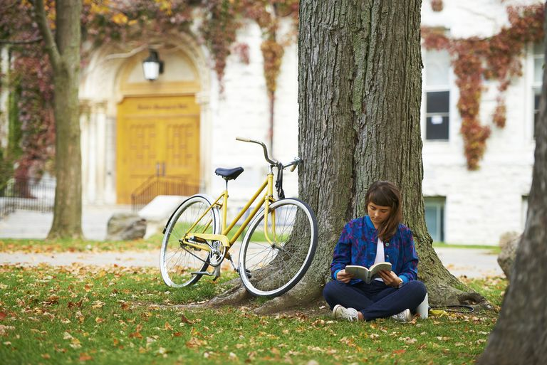 Girl reading book on university campus in fall with yellow bicycle