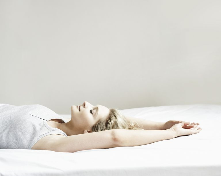 An incredibly satisfied woman lying on a bed