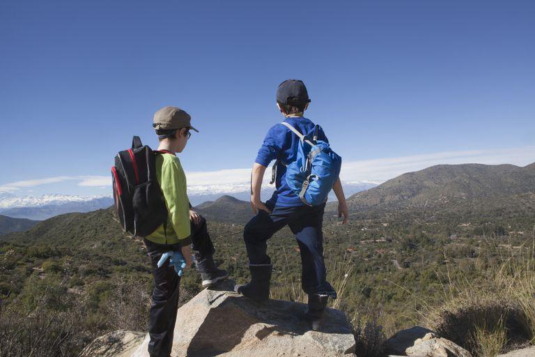 dos niños de pie en una roca mirando a los Andes, Valparaíso, Chile