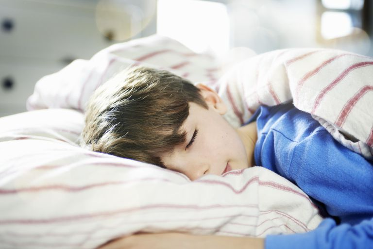 Young boy fast asleep in bed