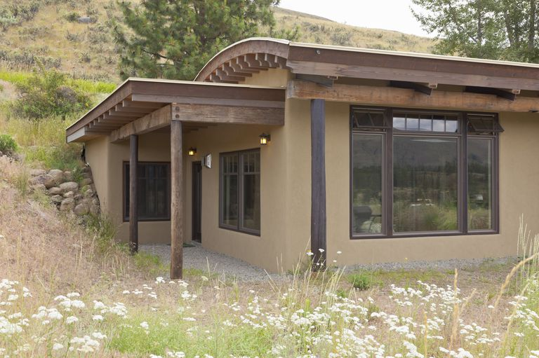 brown-colored adobe single-story house built into a hillside, large windows for natural light, unconventional curved roof