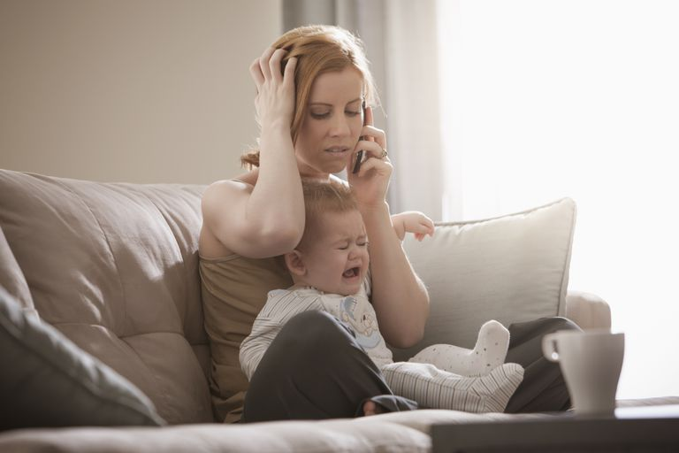 Woman frustrated on the phone while holding baby