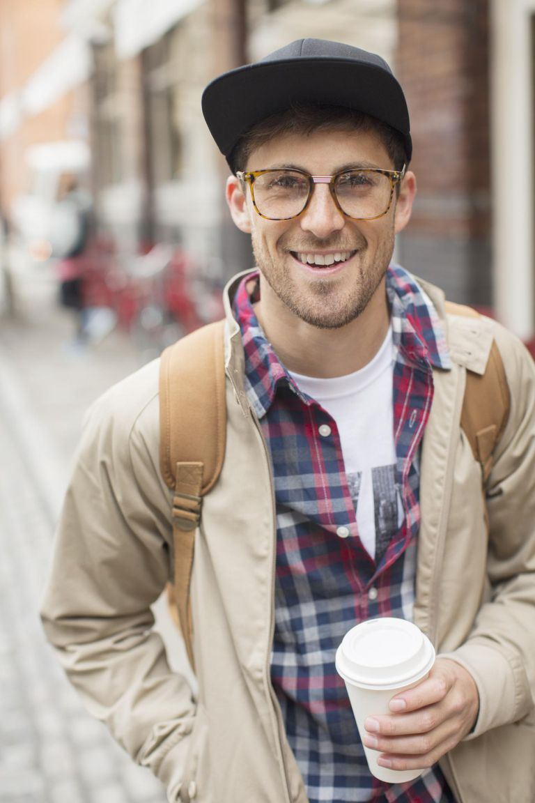 Man with cup of coffee on city street