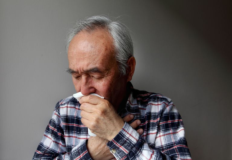 Older man coughing into napkin