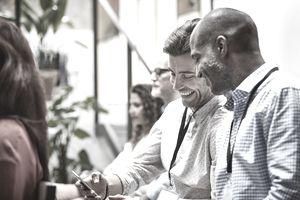 Businessmen using smart phone in seminar