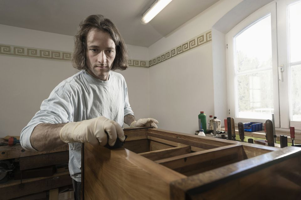 Carpenter French polishing on wooden drawer