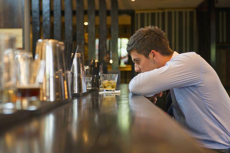 young man drinking at bar alone