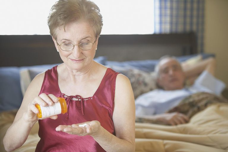 Senior woman holding a bottle of pills