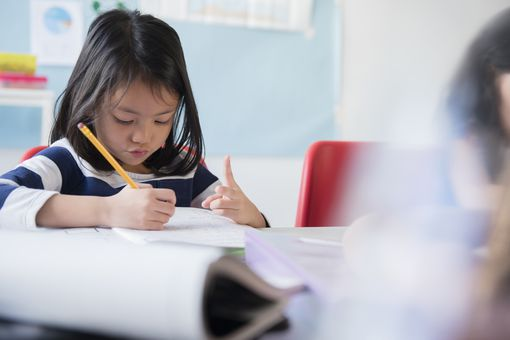 Girl counting with fingers and writing in notebook