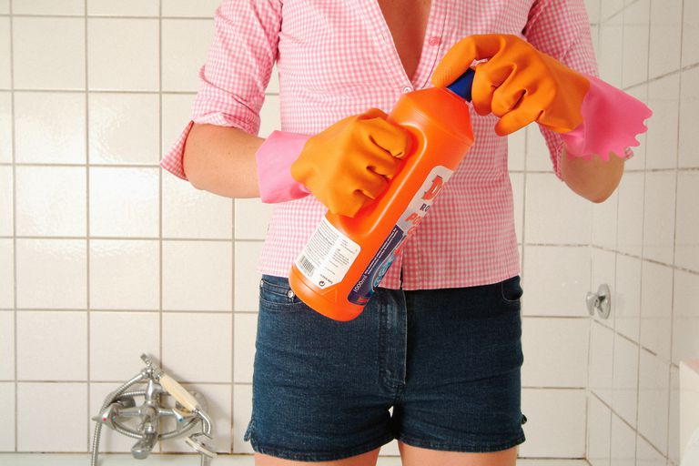woman opening bottle of bleach with cleaning gloves