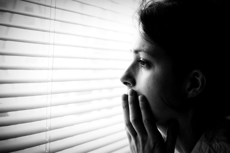 Fearful woman behind blinds