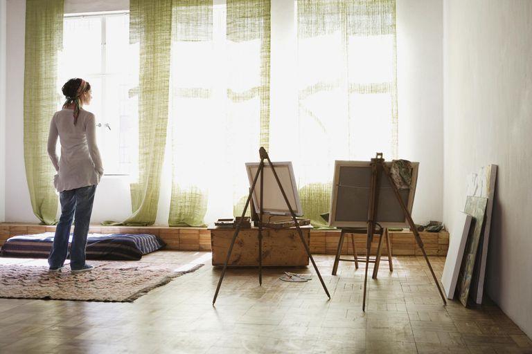 Woman standing in artist's studio, rear view