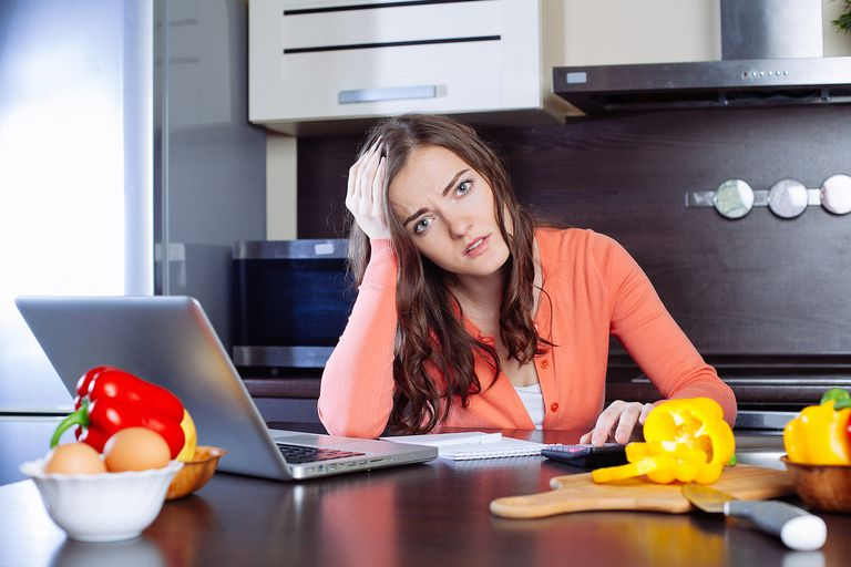 frrustrated woman with laptop at kitchen counter